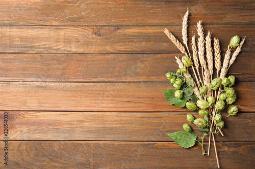 Fresh green hops and wheat spikes on wooden background, top view with space for text. Beer production