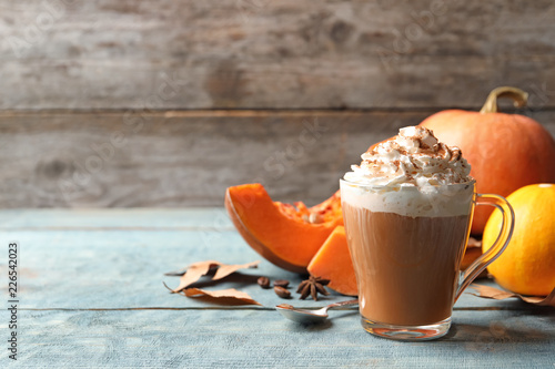 Tableau sur Toile Glass cup with tasty pumpkin spice latte on wooden table