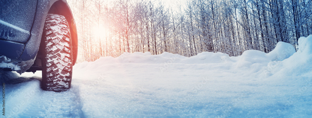 Fototapety, obrazy: Car tires on winter road covered with snow. Snowy landscape with a vehicle