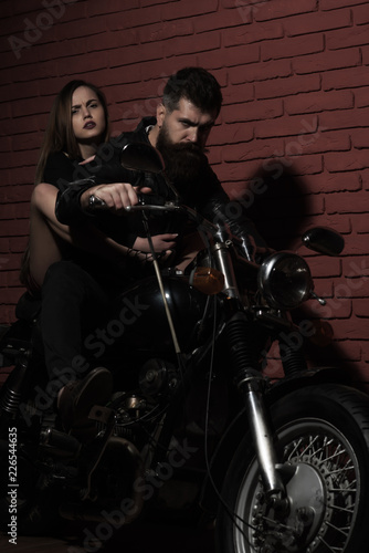 Bearded man and sensual woman ride motorbike, adventure concept Canvas Print