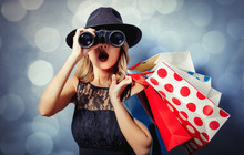 Portrait Of A Young Style Girl In Black Dress And Hat With Shopping Bags And Binoculars On Gray Background With Bokeh