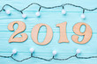 Cut out wooden number 2019 and Christmas lights. Carved wooden digit 2019 in frame from Christmas lights on blue wooden background. Happy New Year 2019.