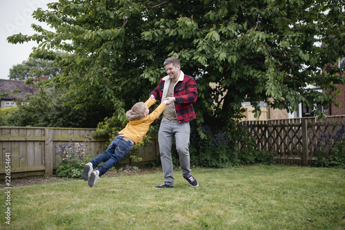 Foto  Father Swinging His Son Around Outside