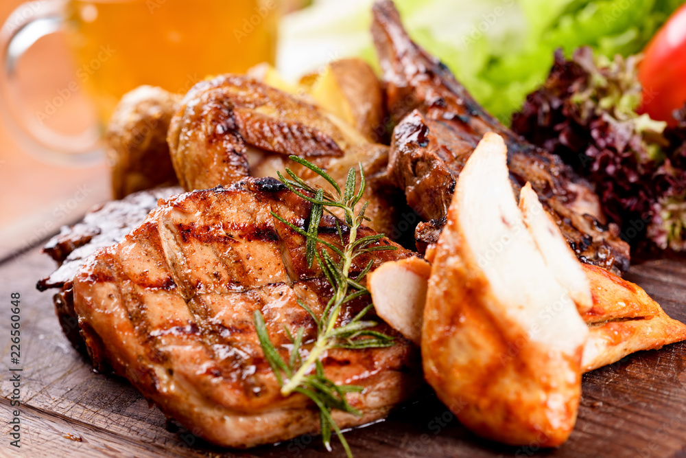 Fototapety, obrazy: Mixed grilled meat and potato on wooden cutting board. Pork, beef, lamb, chicken, quail. Close up
