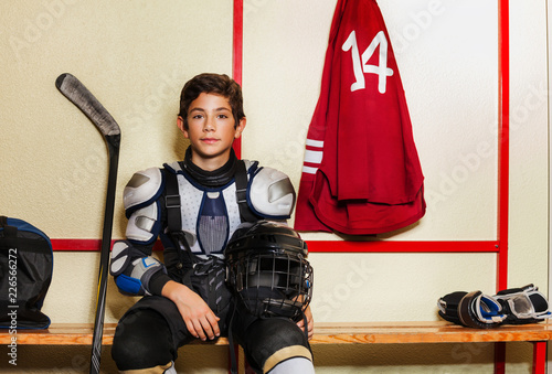 Boy sitting on the bench in ice hockey locker room