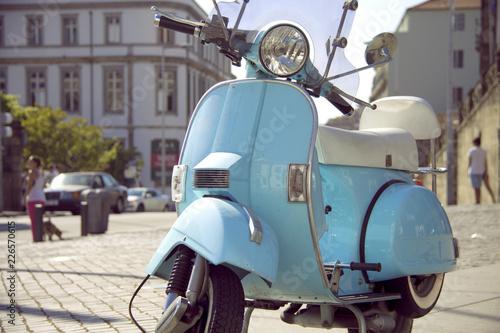 Scooter Motocicleta azul claro aparcada en la calle