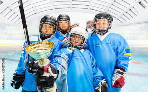 Happy hockey players with trophy on ice rink