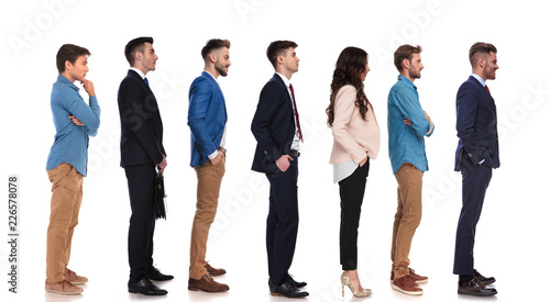 group of seven people with different reactions waiting in line Canvas-taulu