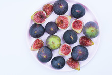 Fresh Figs. Vegetarian Food. Whole And Sliced Figs On A Pink Plate On White Background. Copy Space. Concept Breakfast. Top View.
