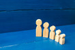 The concept of self-development, growth of personality and professionalism. Children and parents, family. The cycle of human growth. Wooden figures of people from small to large stand in a semicircle.