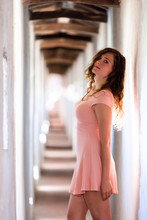 Young Sexy Brunette Girl Woman Closeup In Light Pink Dress Side Profile Standing In Fortress Tunnel, Passage In Italy During Summer, Long Hair Against Wall, Windows