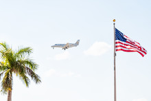 Private Charter Plane Flying Isolated In Sky With American Flag Closeup, Tropical Palm Tree In Naples, Florida