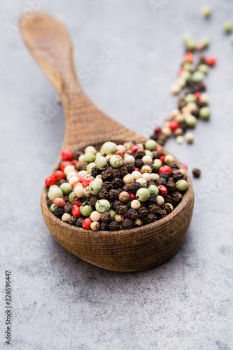 Fotobehang Kruiderij Peppercorn mix in a wooden bowl on grey table.