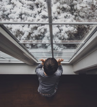 High Angle View Of Boy Looking Through Window At Home During Winter