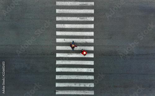 Fototapeta Aerial. Two pedestrians walk on a pedestrian crossing.