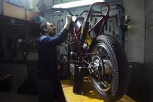 Side View Of Artisan Repairing Motorcycle At Garage