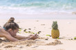 Side view of young woman photographing pineapple on sand at beach