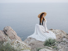 Woman Looking Away While Sitting On Rock Formation Against Sea