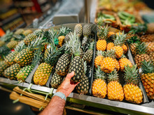 Male Hand Shopping For Pineapple Fruits In Large Fruits And Vegetables Supermarket Store - Choosing The Bio Organic Fruit