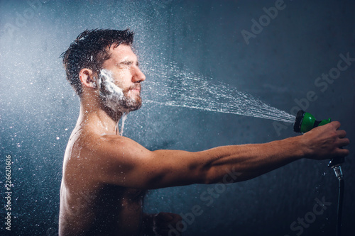 Poster Akt Headshot of a handsome bearded young man with eyes closed, holding a shower head and taking shower, with water splashes all over his face