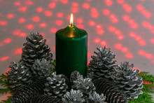 A Single Candle In The Midst Of Silver Pine Cones With Red Lights In The Background