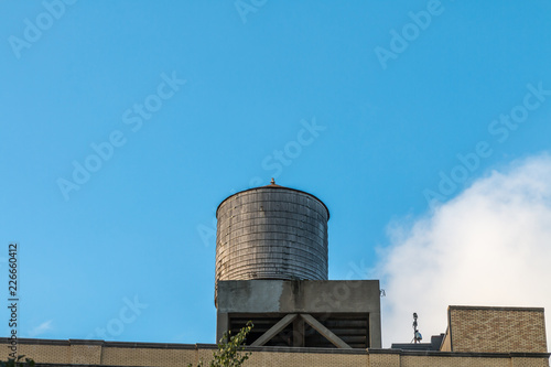 A single wooden water tower stands on a platform on a brick