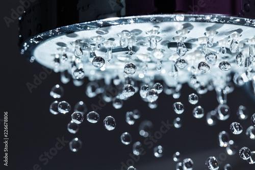 Fotografia  Shower Head with Water Stream on Black Background