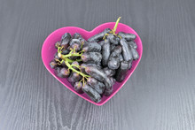 A Heart Shaped Pink Bowl With Long Black Grapes