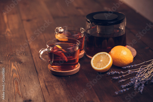 Fototapeta Two full Cup of black tea with lemon and teapot, with lavender, on a brown wooden table, still life obraz