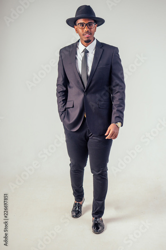 Retro style well dressed African american business man model in dark suit  and black hat in studio on white background 30a27015b74a