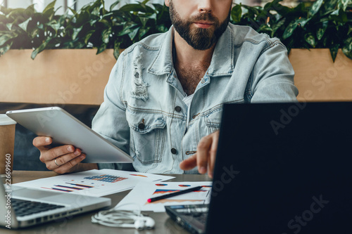 Garden Poster Serious bearded hipster man sitting in office at desk,working on laptop,holding tablet computer,looking at laptop screen