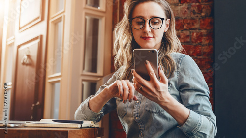 Fotomural  Girl blogger in trendy glasses sits in cafe and uses smartphone,checks e-mail,communicates with followers,reads news