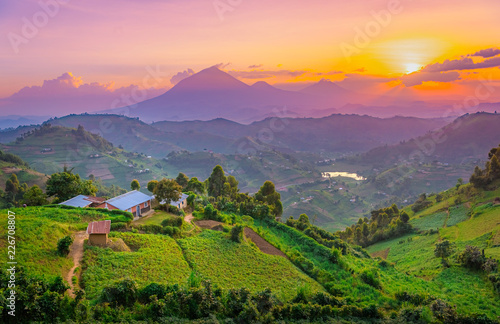 Photo Stands Light pink Kisoro Uganda beautiful sunset over mountains and hills of pastures and farms in villages of Uganda. Amazing colorful sky and incredible landscape to travel and admire the beauty of nature in Africa