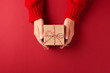 canvas print picture Female's hands in red pullover holding Christmas gift box on red background. Christmas and New Year concept.