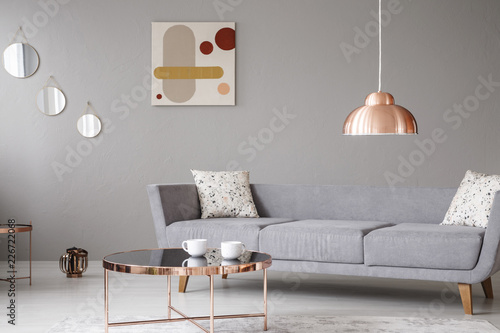 Copper lamp and coffee table in front of a modern sofa in a grey living room interior Canvas Print