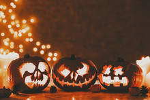 Three Creepy Pumpkins Lanterns Carved For Halloween On Bokeh Background With Copy Space