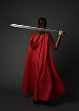 Full Length Portrait Of Brunette Girl Wearing Red Medieval Costume And Cloak. Standing Pose  With Back To The Camera, Holding A Sword On Grey Studio Background.