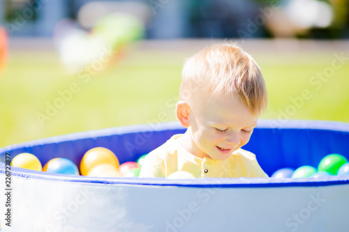 Adorable little boy having fun in the pool with colourful plastic balls