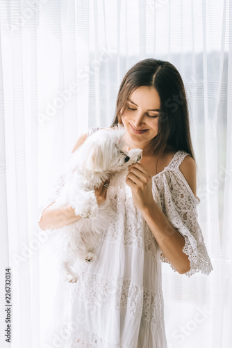 beautiful young woman in white dress playing with adorable bichon dog Wallpaper Mural