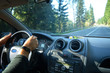 A man driving a car during a country trip through the woods and mountains