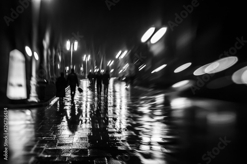 Fotografía  Silhouettes of people like zombie walking at night in the rainy in the light of street lamps,soft blurred focus