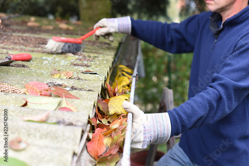Fototapeta Leaves in eaves. cleaning gutter blocked with autumn leaves.