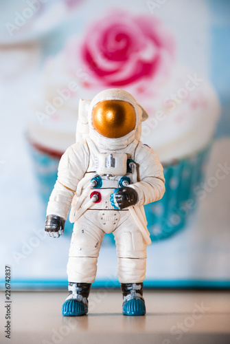 Toy figure of an astronaut, in the background of a cake