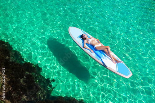 Summer Vacations. Beautiful Young Woman Relaxing on the standup paddleboarding at Turquoise Water. Beauty, Wellness. Recreation.