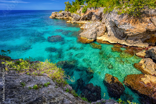 Door stickers Island Beautiful clear turquoise water near rocks and cliffs in Negril Jamaica. Caribbean paradise island and water at the seaside with a blue sky and nice day light