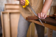 Carpenter saws a board with a hand wood saw. Close-up look on the process of sawing a wooden blank