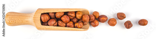 Pile of cracked and shelled hazelnut kernels in wooden scoop on white background.