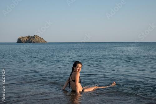 Fotografie, Obraz  teen sitting in water on beach looking at camera