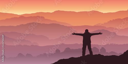 Fotobehang Zalm Un homme alpiniste, contemple le soleil qui se lève à l'horizon d'une chaine de montagne.