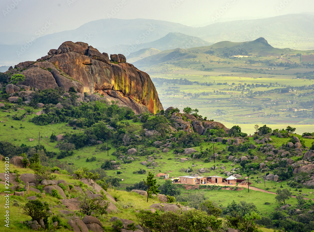 Fototapety, obrazy: Ezulwini valley in Swaziland with beautiful mountains, trees and rocks in scenic green valley between Mbabane and Manzini cities. Traditional huts houses of Swaziland
